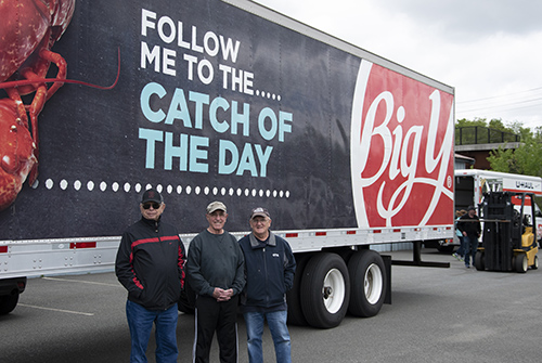 Three volunteers standing in front of a Big Y World Class Market tractor trailer. They are volunteers at the St. John Paul Charity Center in Adams, MA.
