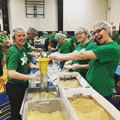 Employees from Berkshire Bank smiling and packing bags of oatmeal