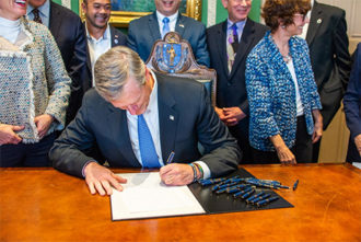 Massachusetts Governor Charlie Baker at his desk signing a bill into law