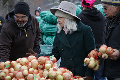 Cheo Ramos, far left, looks over bags of onions with a rep. from Amherst survival center