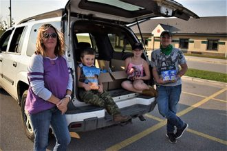 Three children and a parent standing by and sitting in the cargo area of an SUV. They are all smiling.